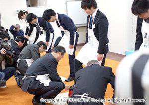 まずは先輩社員が新入社員の靴を磨いてコツやポイントを教えます。