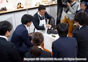 研究員から、靴磨きのレクチャーを受ける新入社員。