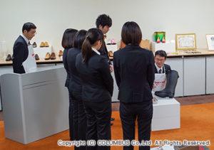 松戸LABOの研究員から、靴みがきのレクチャーを受ける新入社員。